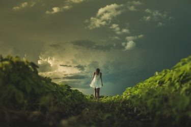 野原に立つワンピース姿の女性