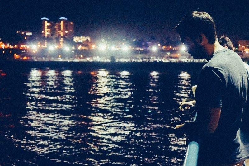 橋から海を眺める男性