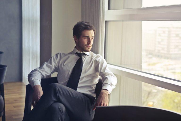 窓の外を眺める座ったビジネスマン
