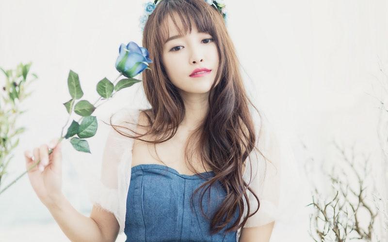 青いバラを持った可憐な女性