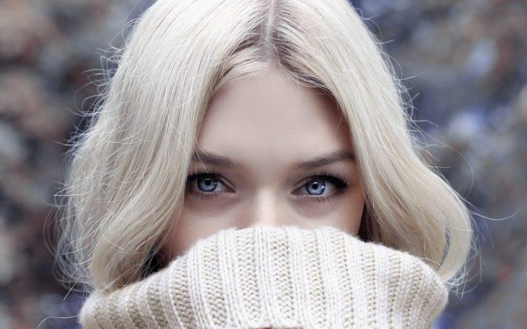 口元を隠したブロンドの白人美人