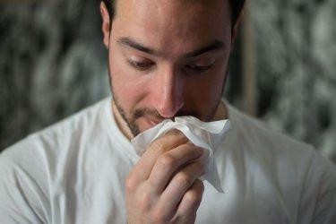 鼻水をティッシュで抑えている男性