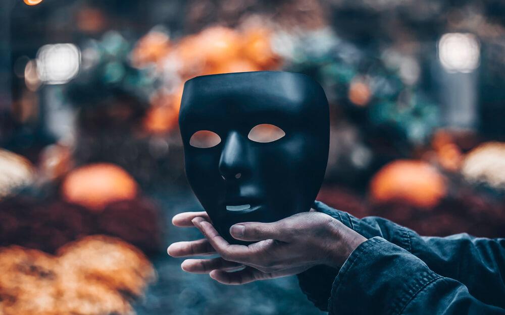 黒いマスクを手に持っている