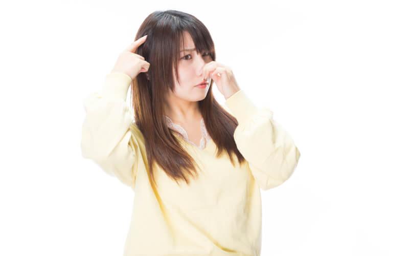 髪を指差し鼻を抑える女性