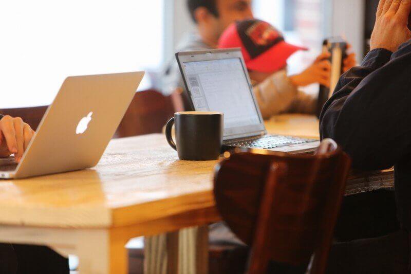 カフェでノートパソコンを開く人たち